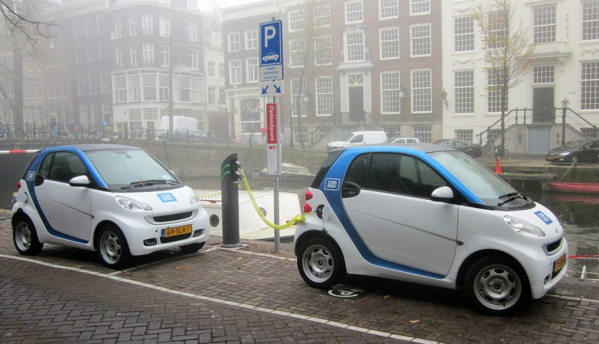 Two Smart Electric Vehicle cars deployed in the Car2Go carsharing program charging at the Herengracht in Amsterdam