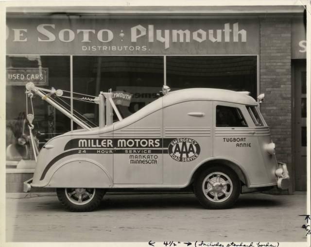1937 International Harvester cab-over-engine (COE) tow truck parked in front of Miller Motors dealership.
