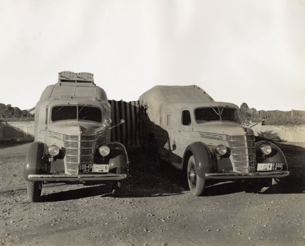 1937 Two specially designed International trucks connected with an awning at an African camp site