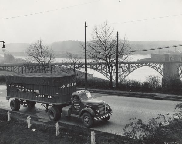 1944 International semi-truck (tractor-trailer) on a road with a hazy view of a bridge