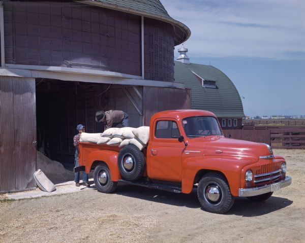 1950 Two men loading bags into a International L-120 truck