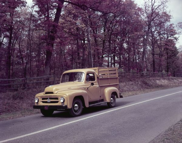 1953 International Harvester standard model R-110 truck with a pickup body and ADA-RAK travels down a wooded roa