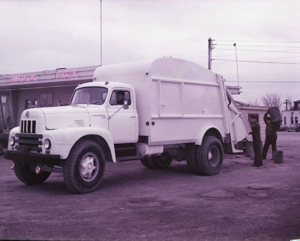 1954 International garbage collection truck parked beside a restaurant