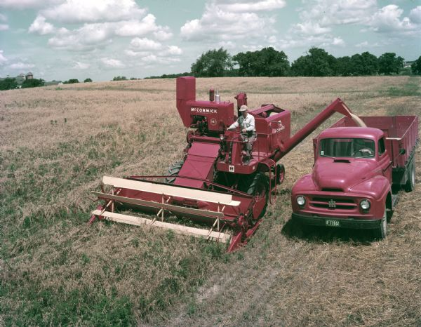 1954 McCormick No. 141 harvester-thresher (combine) and an International truck
