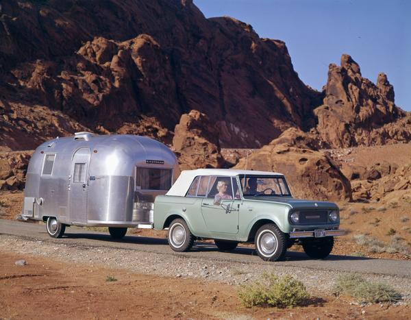 1965 International Scout pickup pulling an Airstream camper in the Nevada hills