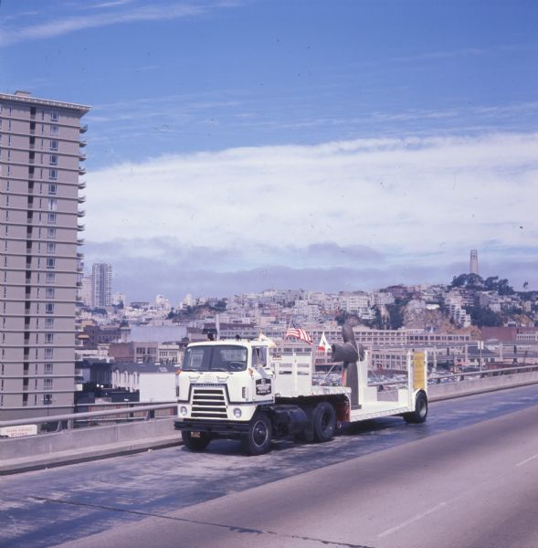 1970 International C-O 4070A Transtar truck hauling the metal statue St. Francis of the Guns on a trailer down a San Francisco highway