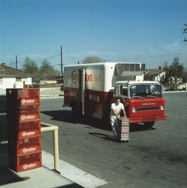 1972 Color photograph of a man unloading cartons of milk from an International truck used by the Carnation Company. The truck appears to be an Internati