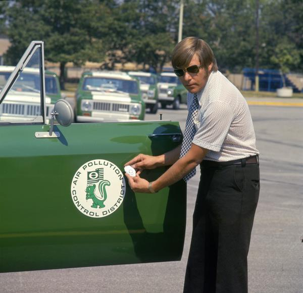1975 air pollution inspector wearing sunglasses is holding his badge near the door emblem on his International Scout II pickup