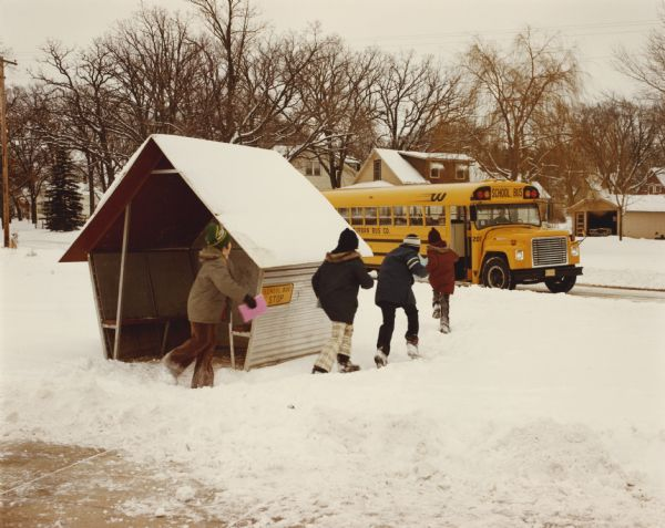 1975 kids walking through snow while leaving a metal bus shelter to board an International school bus