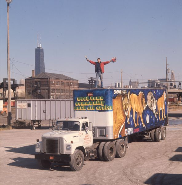 1975 Man Standing Atop Truck Trailer with Big Cat Mural
