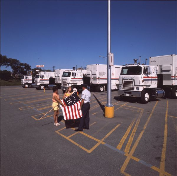 1976 International Woman, Young Woman, and Man with '76 Flag and Trucks