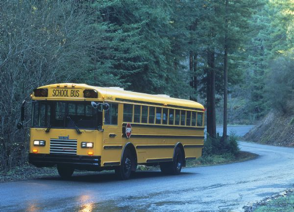 1988 IH School Bus Driving through Wooded Area