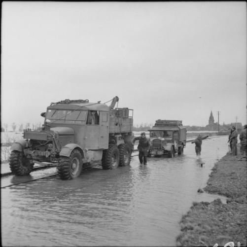 1945 Fordson WOT2 15cwt truck, marooned on a flooded railway line near Kranenburg, is towed to safety by a Scammell Pioneer recovery vehicle, 14 February 1945