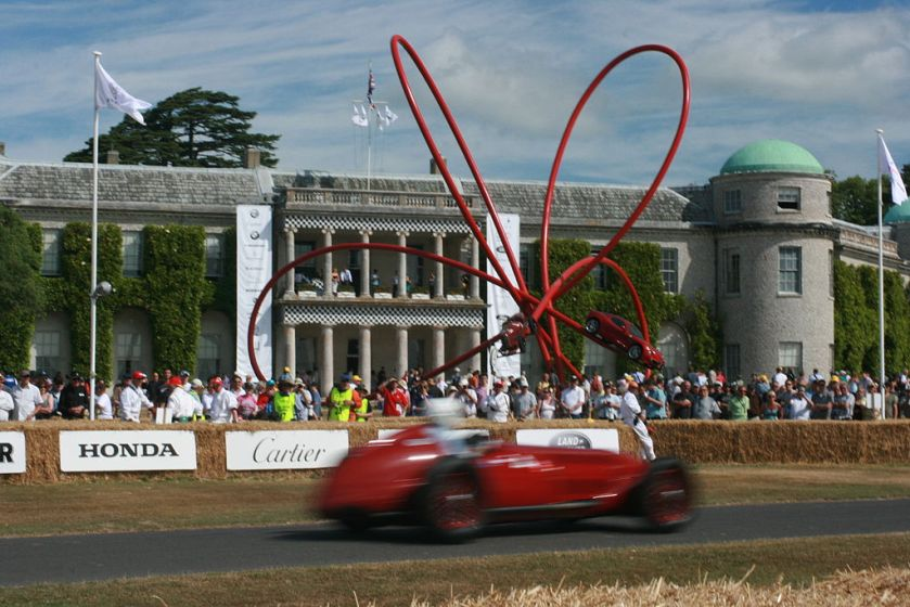 Alfa Romeo at speed past Alfa Sulpture at Goodwood House