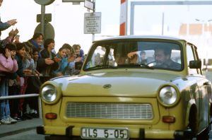 1989 West German children applaud as an East German couple drive through Checkpoint Charlie and take advantage of relaxed travel restrictions to visit West Germany